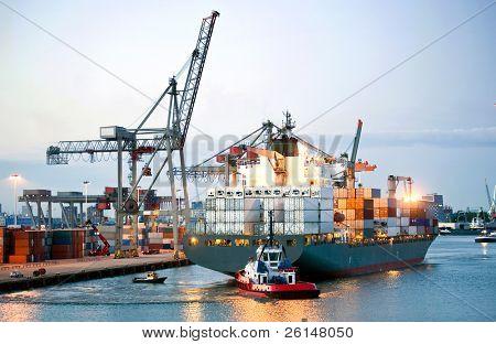 Ah enorme navio de recipiente sendo manobrado e revertido para a costa por pilotos e rebocadores