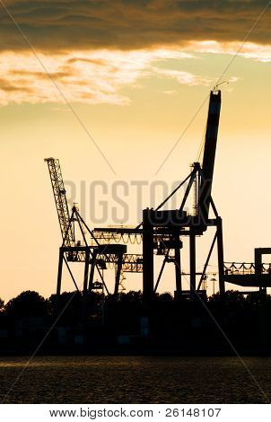 Silhouettes of two motionless, erect, idle harbor cranes against the setting sun