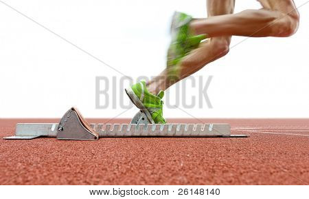 Action packed image of an athlete leaving the starting blocks for a sprint run on a track