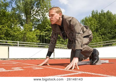 Young businessman, ready to start his career, visualized by getting ready for a sprint run in the starting blocks with a determined look in his eye
