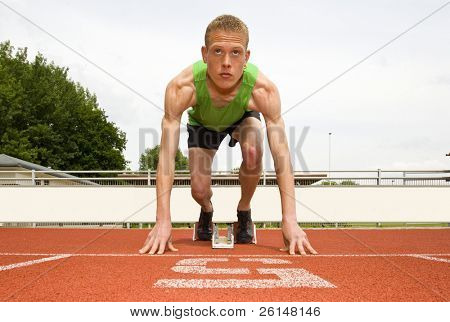 Athlete in lane five, set to start in the starting blocks for a sprint run