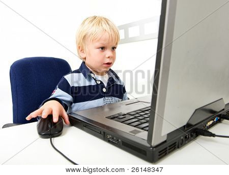 A young boy sits using a laptop computer. He is viewable from the chest up and is looking away from the camera at the laptop screen. Horizontally framed shot.