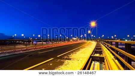 Cars passing by on a motorway junction on a winter evening