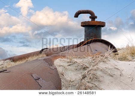 An old, obsolete pipeline with a faucet and flanges, surrounded by the drift-sand and marram grass of the dunes against a radiant cloudscape.