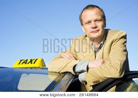 A taxi driver posing behind the front door of his cab