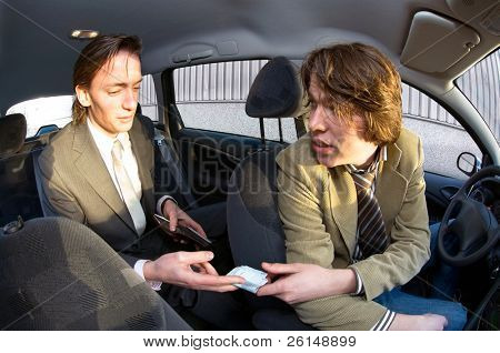 A businessman paying the fare to the taxi driver