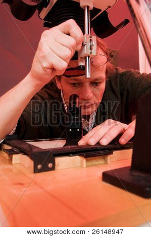 Photographer in a darkroom fine tuning the focus of the enlarger, peering through a focus scope