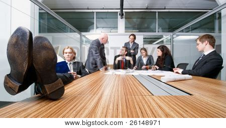 Young businessman, sitting with his feet resting on the table, obviously bored with what's happening in the meeting he's attending - completely demotivated and disinterested.