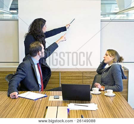 Two colleagues pointing at a presentation screen, trying to convince a bored looking businesswoman
