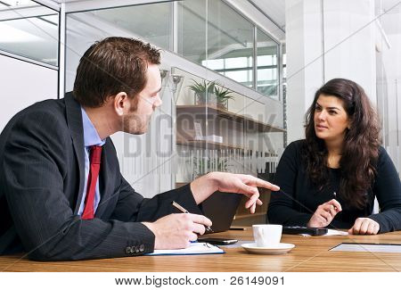 Two colleagues in a cubicle discussing strategy