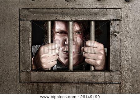 Bild von einem Mann in Haft halten die Gitterstäbe seiner Zellentür Kreuz.
