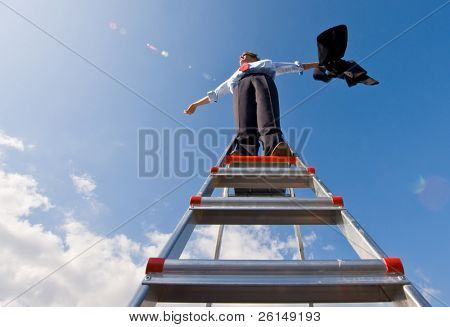 A businessman spreading his arms in the wind, standing on top of a ladder, whiles holding his jacket.