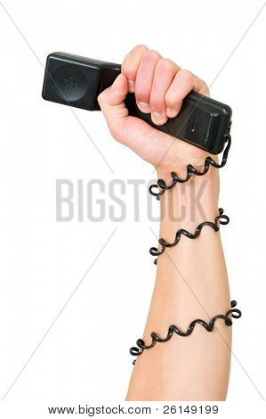 Arm and clenched fist, holding a telephone, with the wire wrapped around the arm, illustrating the power of a telephone service, call center or phone terror