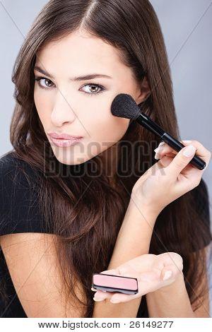 Woman doing makeup with powder brush
