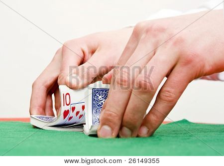 Dealer's hands shuffling cards during a poker game