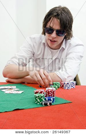 A man, wearing large sunglasses,  playing a tricky game of poker