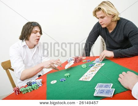 A poker player folding his game by tossing his cards out on the table