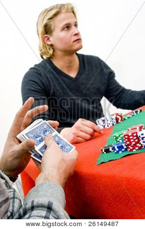 A card player shuffling cards during a poker game with one of his competitors in the background - Selective focus on the hands