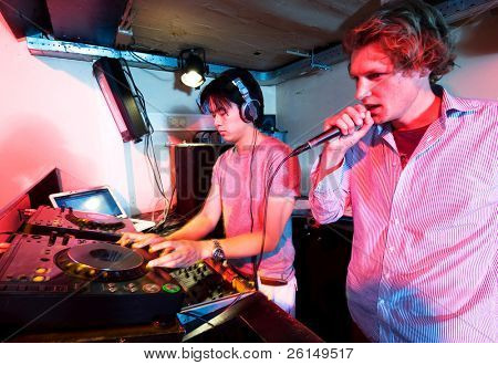 A DJ and a mc in action at a party in a nightclub.
