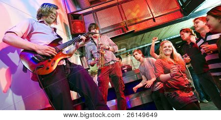Guitarist and saxophone player, accompanied by a DJ, during a gig with an enthusiastic crowd in a discotheque