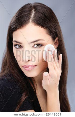 Pretty Black Hair Woman Applying Make Up On Her Cheek