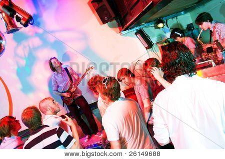 Gitarrist auf der Bühne in einem Nachtclub, mit Partei Menge, Saxophonist und dj
