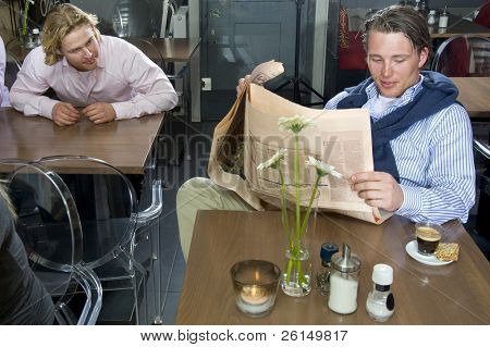 A man trying to catch a glimpse at the paper of a man sitting at another table