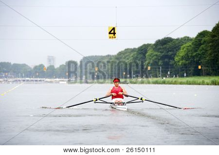 Man, rowing in a skiff during a race  at full speed
