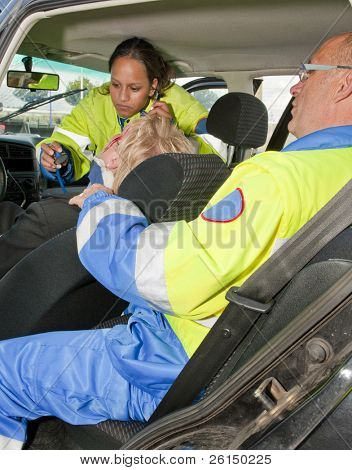 Paramedics providing first aid to an injured woman in a car