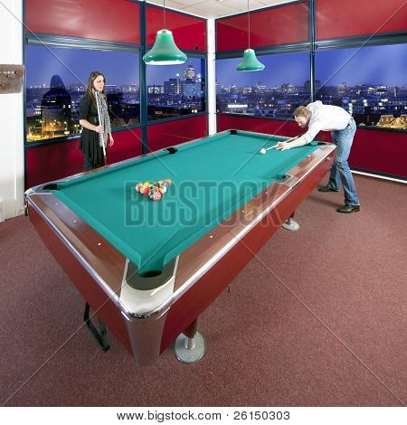 Two people playing pool in a room with a view on an city skyline at dusk