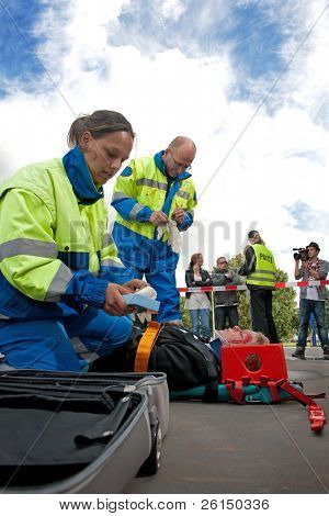 Paramedics tending to the first aid of an injured woman on a stretcher at the scene of a car crash, whilst a police woman talks to the bystanders behind the cordon tape, being filmed by a camera man