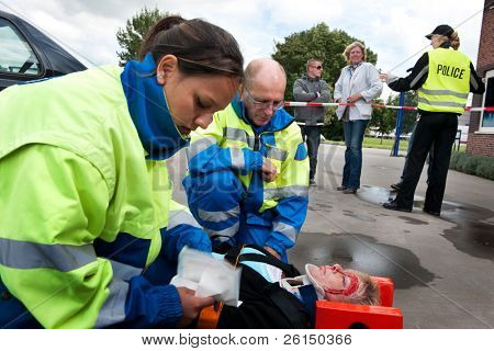 Paramedics providing first aid to an injured woman with police and bystanders in the background