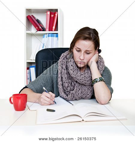 Tired young woman staring aimlessly at her books, trying to study