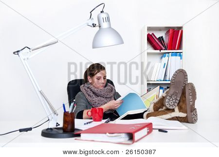 Young woman studying tirelessly, flipping through a folder with her feet on her desk - the background is off-white