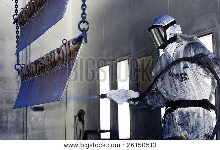 Hombre en un traje de protección, que llevaba un semi de acero de pintura a pistola de careta antigás terminado de piezas en un productio