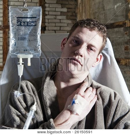 Very sick man, with an IV drip sitting in a chair