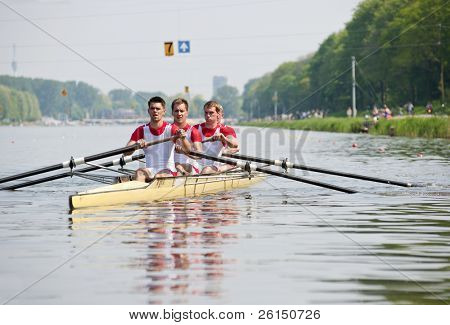 Coxed four rowing team paddling backwards to the start, with concentrated looks in their eyes, in anticipation of the race ahead