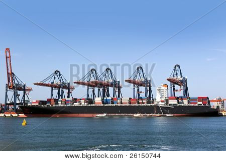 Container ship being unloaded at an industrial harbor