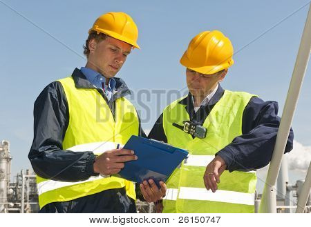 Two petrochemical engineers wearing safety vests and a hard top going over a checklist