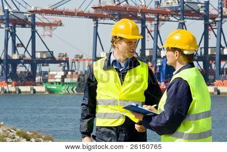 zwei Hafenarbeiter bei der Arbeit in einem großen Container-Hafen