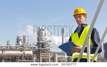 Young supervisor with a note board and pen in his hands, wearing a hard hat and safety vest in front of a petrochemical plant and refinery