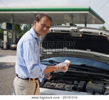 Hombre comprobar los niveles de aceite en su coche en una gasolinera, utilizando una tira reactiva