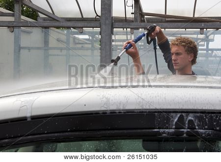 Man washing his car with a high pressure water jet