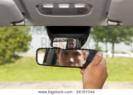 Man, adjusting the rear view mirror of his car