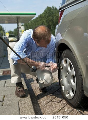 Man, inflating a tire and checking for the proper air pressure in the wheels of his car