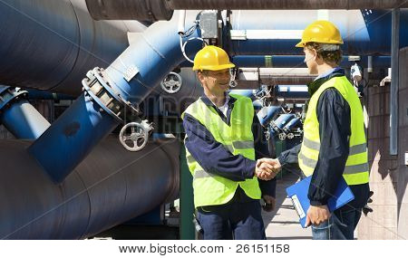 Two engineers meeting outside at the piping of an industrial waste water cleaning facility