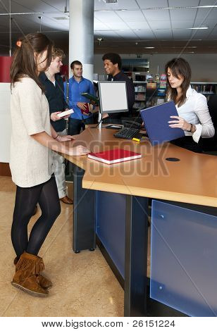 A queue of customers waiting at the check out desk, where a librarian is scanning books