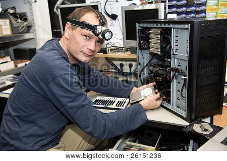 Man with a LED light on his head, working on a desk top computer in a computer repair shop