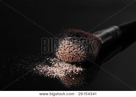 Make up brush with powder isolated on black