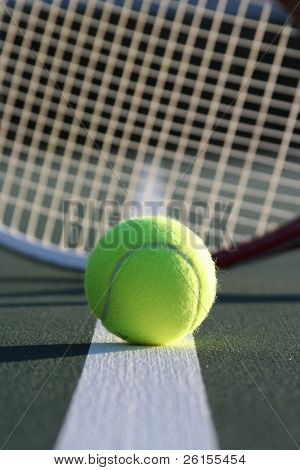 Tennis ball with a racquet in the background